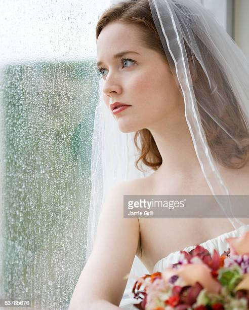 Bride looking out window on a rainy day