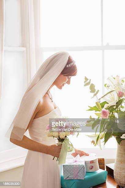 Bride looks at gift.