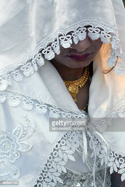 A bride looks down during a mass wedding ceremony in the grounds of ancient Babylon some 100 kms south of Baghdad on December 01 2008 Some 200...
