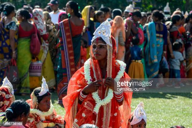 A bride looks on as she takes part along with other brides and grooms from the Adivasi tribe in a mass marriage ceremony during a religious...