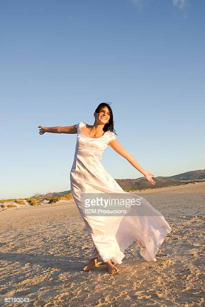 Bride on beach with arms up