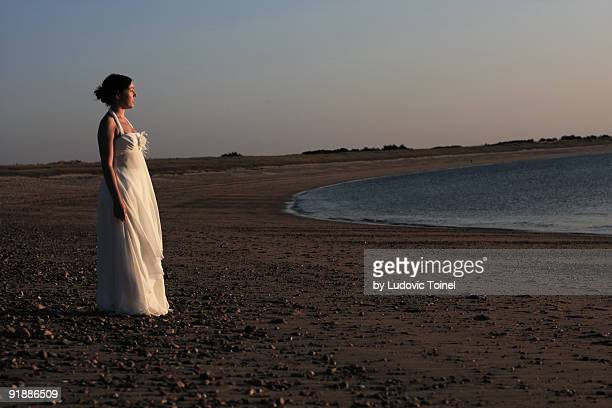 a bride on the beach - ludovic toinel stockfoto's en -beelden