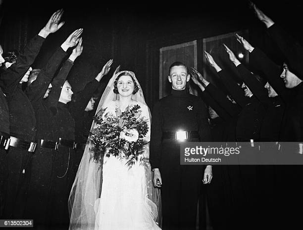 Bride Pamela Dorman passes through a line of men performing a Nazi salute with her groom Ian Dundas chief of staff of the British Union of Fascists...