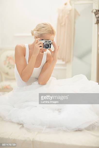 Bride photographing with vintage camera on bed