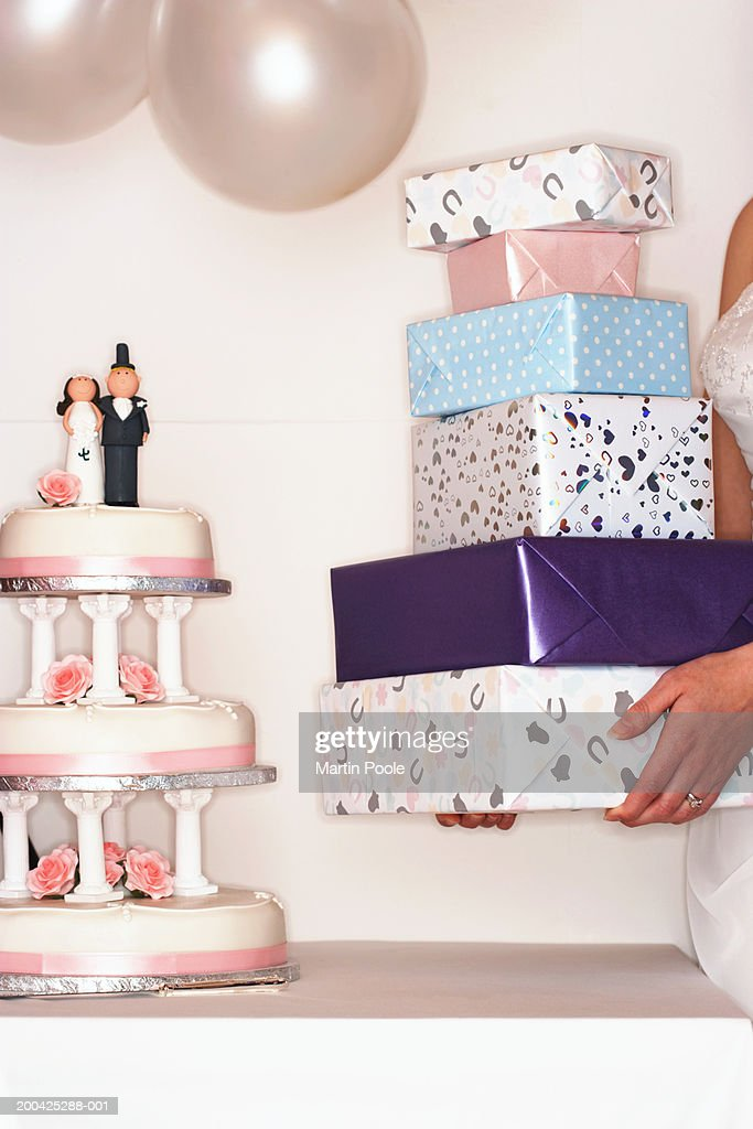 Bride placing presents on table by wedding cake : Stock Photo