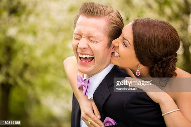 bride playfully biting groom in his earlobe - earlobe stock photos and pictures