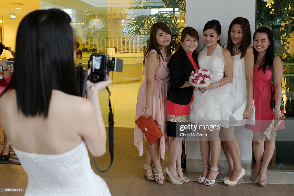 A bride poses for a photograph with friends outside the Singapore Registry for Marriage on December 12, 2012 in Singapore, Singapore. Today saw a surge in marriages across the globe with the Singapore Registry for Marriages inundated with over 500 couples applying to be married on the auspicious and once in a century date of 12.12.12.