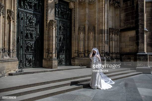 A bride poses for her photographer in front of the St Vitus Cathedral on May 9 2016 in Prague Czech Republic Ruler Charles IV began the construction...