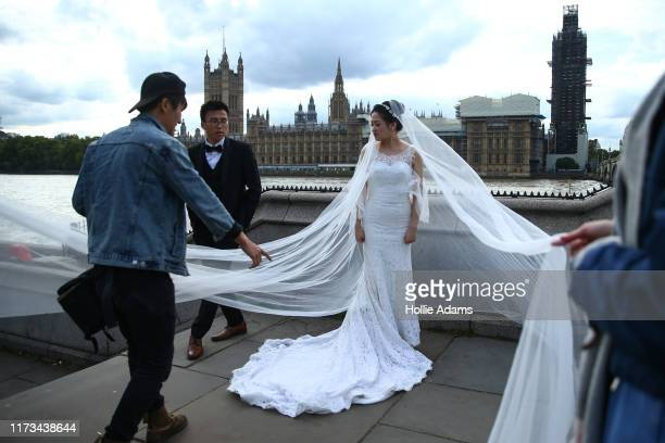 A bride poses for photographs opposite the Houses of Parliament on October 3 2019 in London England