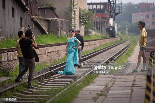 A bride poses for photos on disused railway tracks in the 798 art district previously the site of various electronics factories in Beijing on July 19...