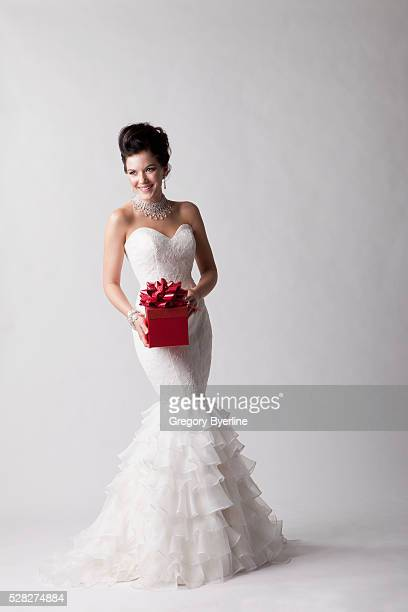 a bride posing with a red gift against a white background; nashville tennessee united states of america - wedding dress stock pictures, royalty-free photos & images
