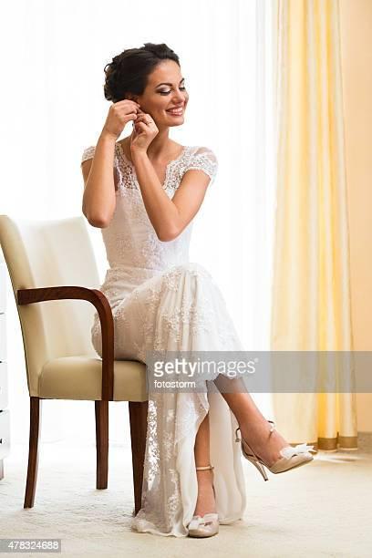 Bride preparation, putting earrings on