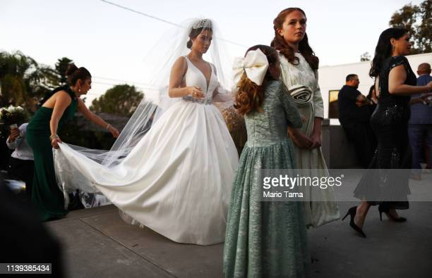 A bride prepares to enter the church for her wedding near the USMexico border on March 30 2019 in Tijuana Mexico US President Donald Trump told...