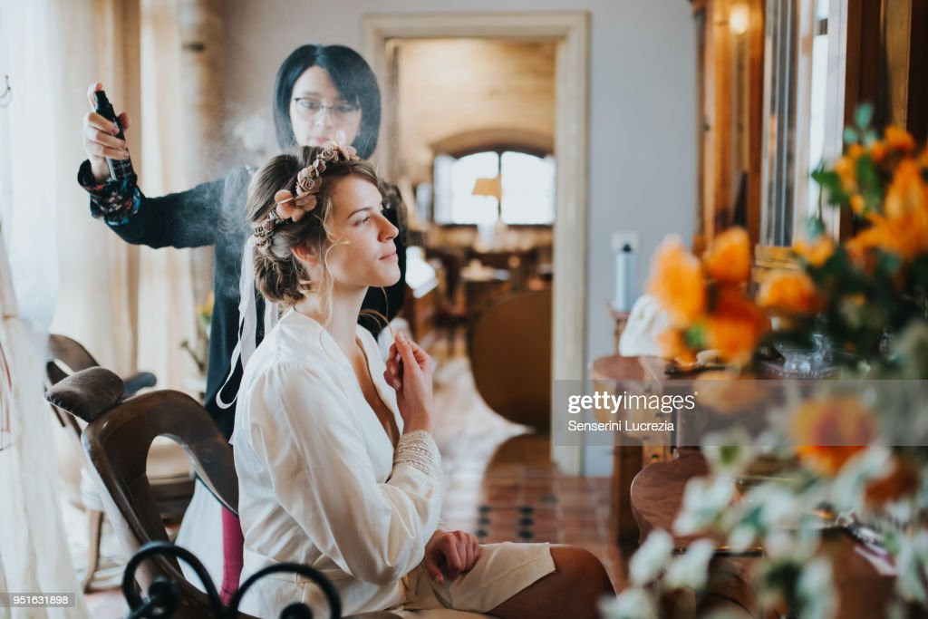 Bride preparing for wedding with hairstylist : Stock Photo
