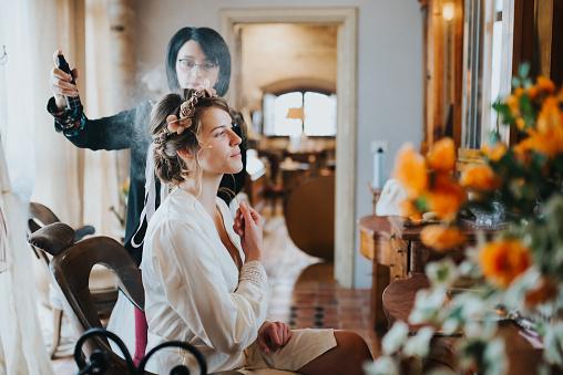 Bride preparing for wedding with hairstylist - gettyimageskorea