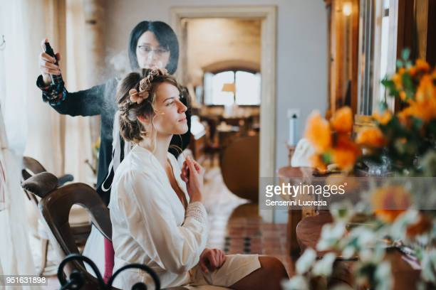 Bride preparing for wedding with hairstylist