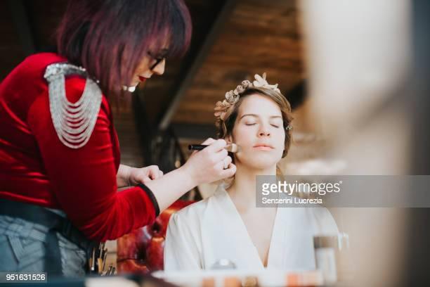 Bride preparing for wedding with make-up artist