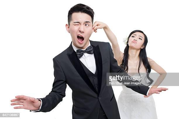 Bride pulling grooms ear