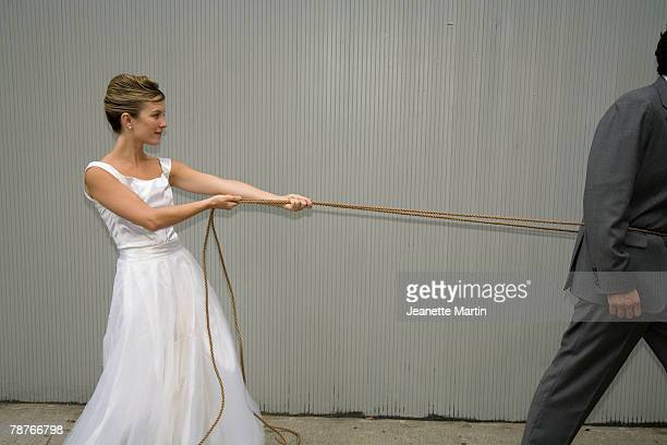 A bride pulling the groom with a rope