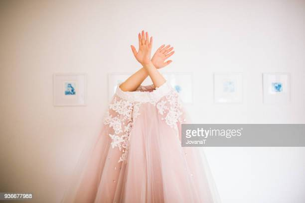 bride putting her wedding pink  lace dress over her head - frilly stock photos and pictures