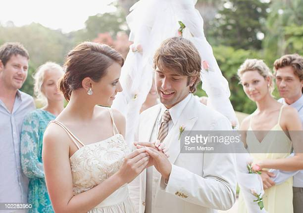 Bride putting ring on grooms finger