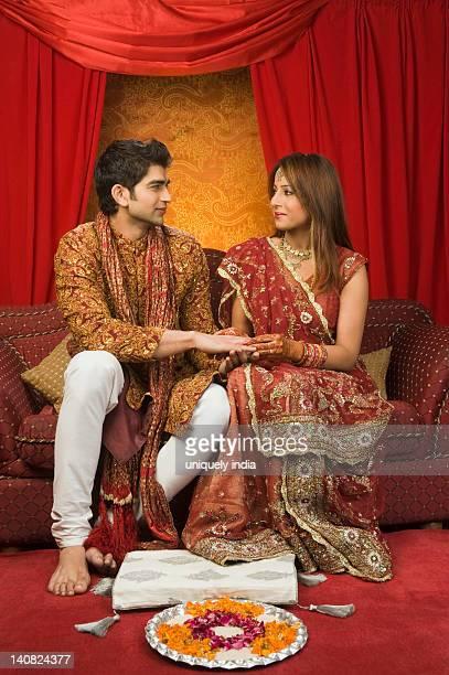 Bride putting wedding ring on groom's finger