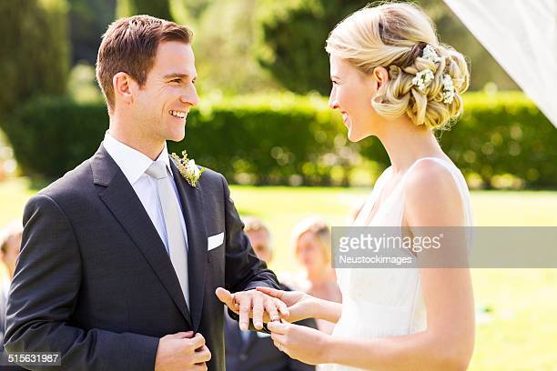 bride putting wedding ring on groom's finger - wedding vows stock pictures, royalty-free photos & images