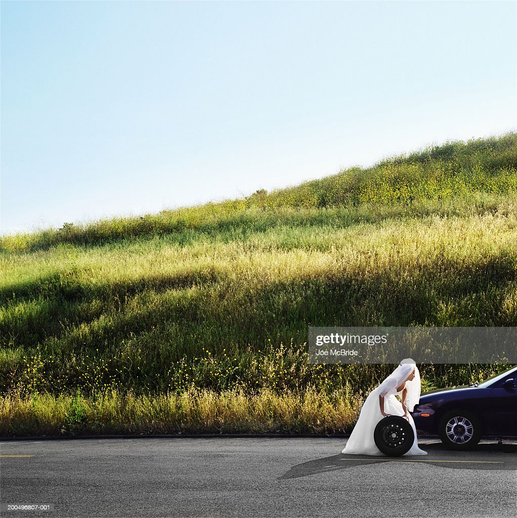 Bride Rolling Car Wheel On Side Of Road View Stock Photo