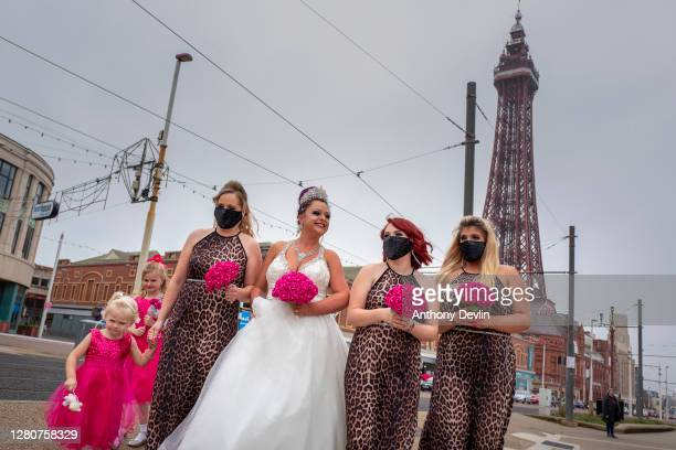 Bride Rosie Graham walks along the Promenade with her bridesmaids wearing face masks on October 17, 2020 in Blackpool, England. Lancashire has...