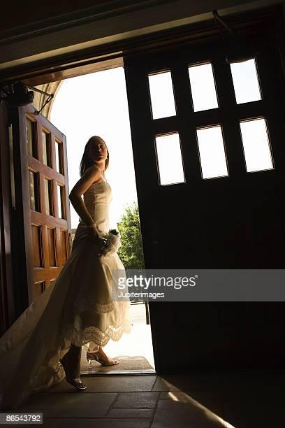 Bride running through doorway