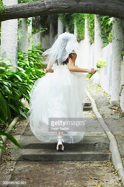Bride running up path, rear view