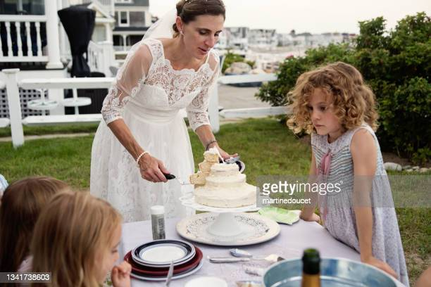 """bride serving the homemade cake at small wedding celebrations. - """"martine doucet"""" or martinedoucet stock pictures, royalty-free photos & images"""