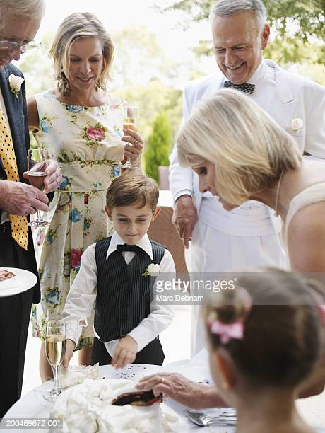 Bride serving wedding cake to pageboy (6-7) and guests