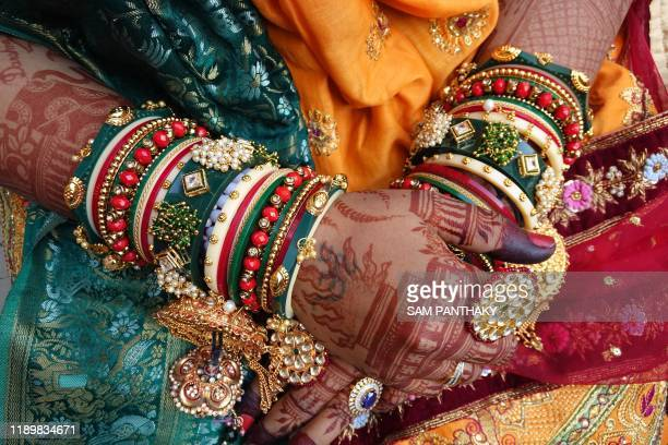 A bride shows her hands decorated as she participates in a mass wedding ceremony in Surat some 270 km from Ahmedabad on December 21 2019