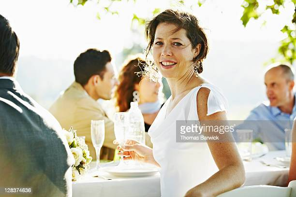 Bride sitting at banquet table outside in field