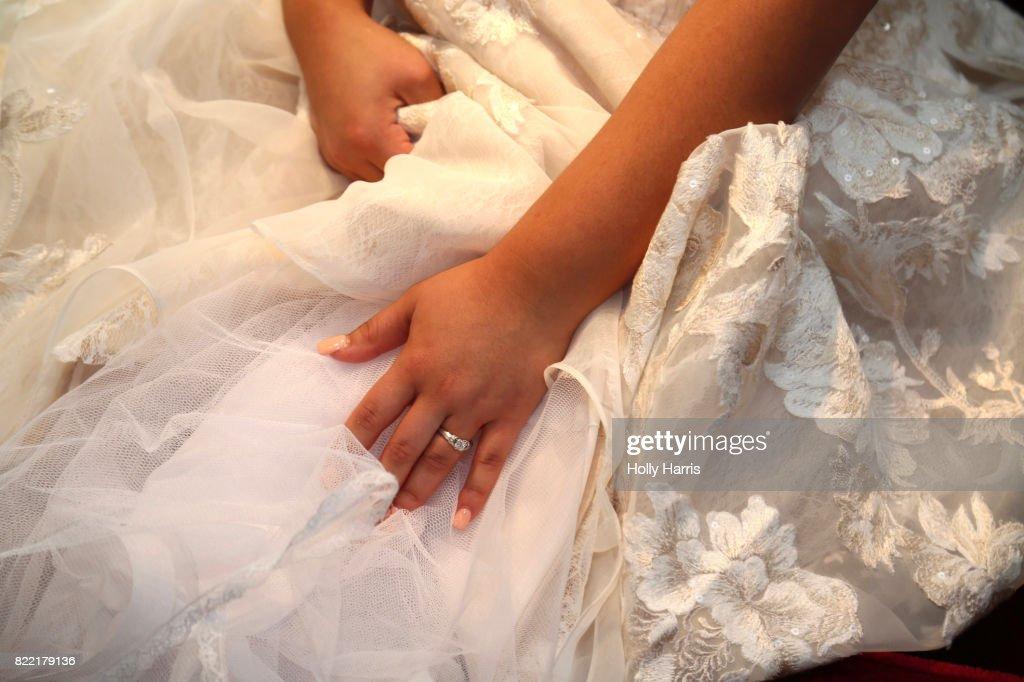 Bride sitting, holding her dress : Stock Photo