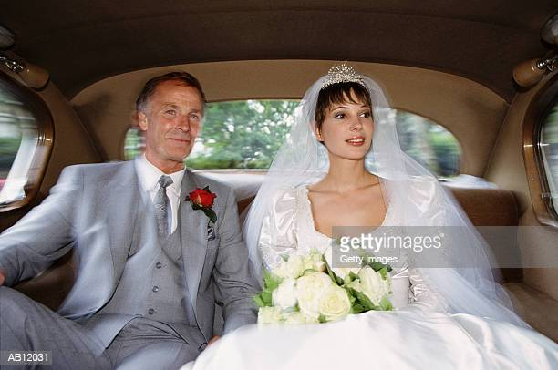 Bride sitting in back of limousine with father