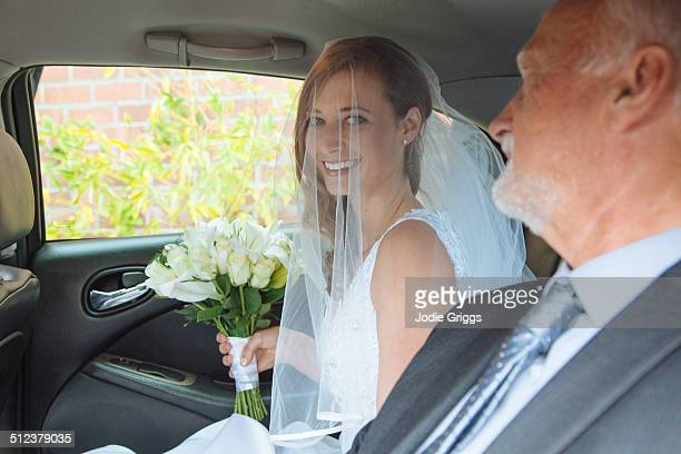 Bride sitting in car with Father on way to wedding