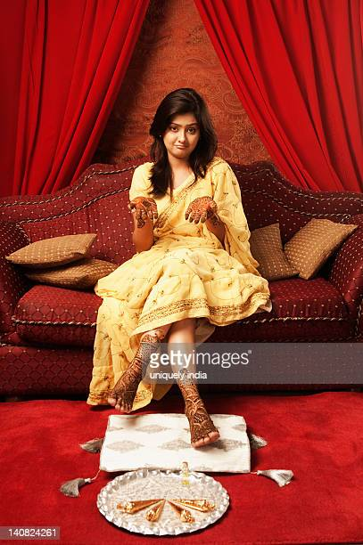 bride sitting on a couch with henna decoration - beautiful female feet stock photos and pictures