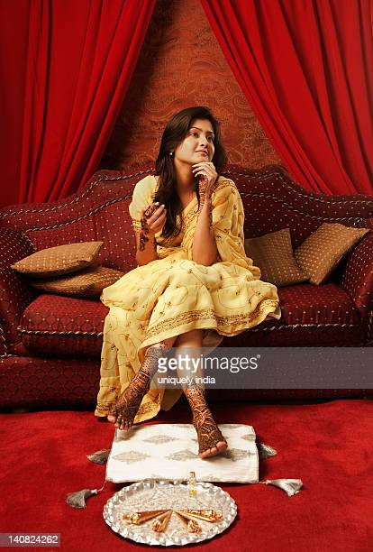 bride sitting on a couch with henna decoration - pretty asian feet stock photos and pictures