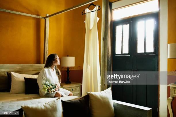 bride sitting on bed and holding bouquet in hotel room before wedding - verlangen stockfoto's en -beelden
