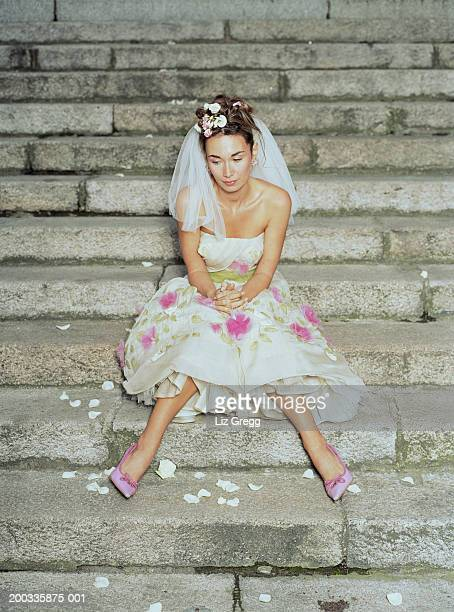 Bride sitting on steps, resting hands in lap, looking downwards