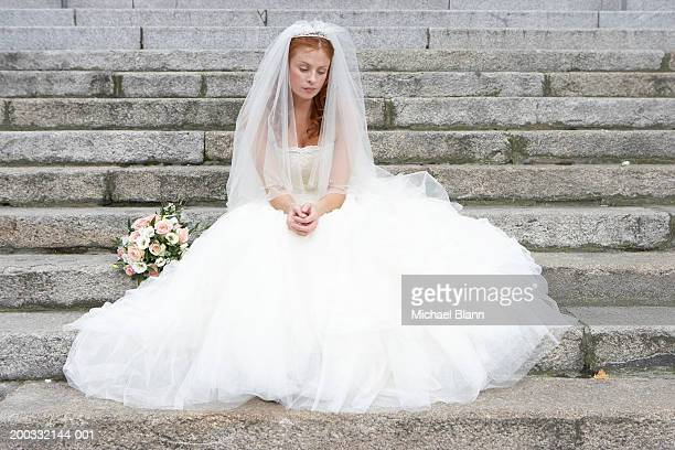 bride sitting on stone steps, looking towards ground - veil stock pictures, royalty-free photos & images