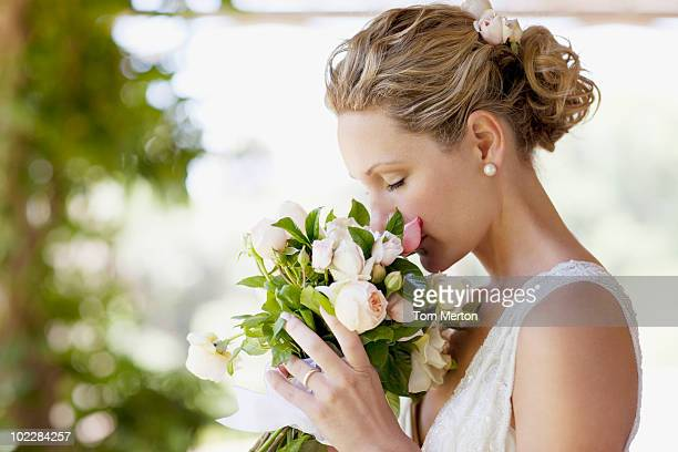 bride smelling bouquet - mid adult women stock pictures, royalty-free photos & images