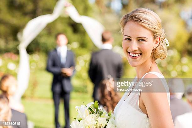 Bride Smiling During Wedding Ceremony In Garden