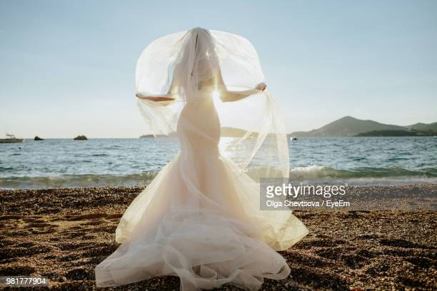 bride standing at beach against sky - bride stock pictures, royalty-free photos & images