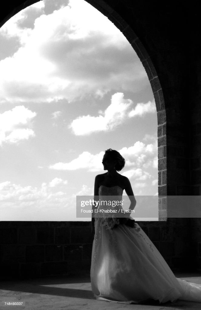 Bride Standing By Arch Window : Stock Photo