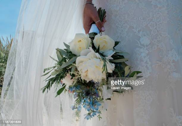 bride standing in her lace wedding dress holding her bouque of flowers - obscured face stock pictures, royalty-free photos & images