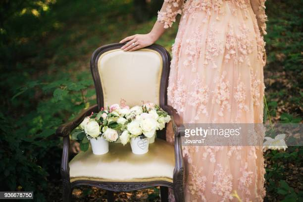 bride standing next to armchair with flowers on it - pink dress stock pictures, royalty-free photos & images