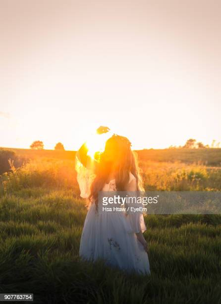 Bride Standing On Grassy Field Against Sky